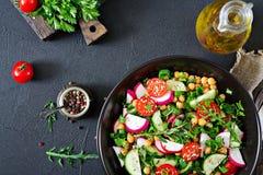 Salad of chickpeas, tomatoes, cucumbers, radish and greens. Dietary food. Vegan salad. Top view. Flat lay Stock Photos