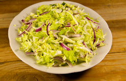 Salad with chinese cabbage and onion on wooden table Stock Photo