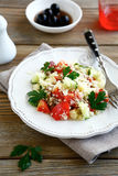 Salad with cooked couscous and vegetables on a white plate Stock Photo