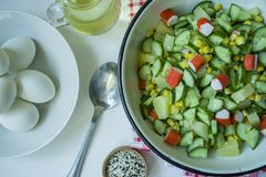 Salad with corn, crab sticks, cucumbers in a white bowl on a white background. Vegetarian salad. Cooking process stock photo