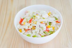 Salad with corn and crab sticks in white dish on wooden background. Selective focus stock image