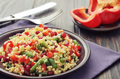 Salad with couscous and vegetables. Salad with couscous, sweet pepper, green bean, pomegranate and sesame on plate closeup Royalty Free Stock Photography