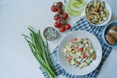 Salad with crackers, crab sticks, chicken fillet, fresh herbs and hard cheese seasoned with olive oil served in a white plate. stock images