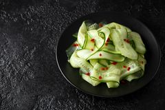 Salad of cucumber slices with salt, pepper and red pepper royalty free stock images
