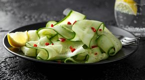Salad of cucumber slices with salt, pepper and red pepper stock photos