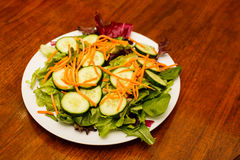 Salad with Cucumbers and Carrots on Wood Table. A fresh salad of sliced cucumbers and shredded carrots on field greens on a white plate Stock Photos
