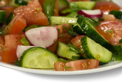Salad with cucumbers and tomatoes. On a plate. On a white background Stock Images