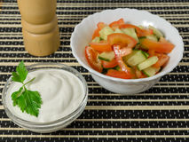 Salad with cucumbers and tomatoes and sour cream. Stock Photography