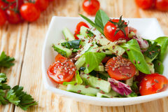 Salad of cucumbers and tomatoes on a wooden table Stock Photo