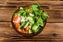 Salad with cucumbers and tomatoes on wooden table Stock Photos