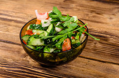 Salad with cucumbers and tomatoes on wooden table Stock Photography