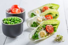 Salad decomposition in chicory with avocado, asparagus and peas. On white table stock photography