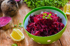 Salad: diet salad with beetroot, olive oil and lemon. Served in a bowl on wooden background. Beetroots, lemon and lettuce on kitchen table Royalty Free Stock Image