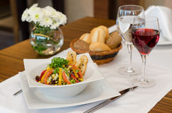Salad. Dining table setting with salad, wine, bread and flowers Stock Photos