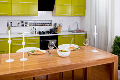 Salad on the dinner table with pasta and wine glasses on kitchen Royalty Free Stock Photography