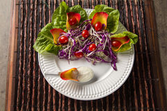 Salad dish with grape tomatoes, lettuce and red cabbage and sauc Royalty Free Stock Images