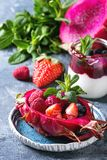 Salad in dragon fruit. Vegan fruit salad with berries and mint served in pink dragon fruit with ingredients above on ceramic plate over blue texture background Stock Images
