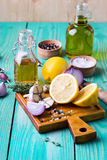 Salad dressing ingredients. Ingredients for the preparation of salad dressing. Onions, garlic, lemon, spices and thyme on a green wooden board stock image