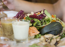 Salad with dressing on the next plate Royalty Free Stock Photography