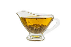 Salad dressing with olive oil in glass sauce boat. Over white background royalty free stock photography