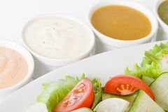 Salad & Dressings. Salad with cucumber, tomato, onions and lettuce served with four sauces Stock Photos