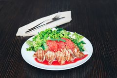 Salad of duck breast with grapefruit on a white plate. Background wooden table royalty free stock photography