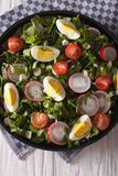 Salad with eggs, radishes and sorrel closeup. vertical top view. Spring salad with eggs, tomatoes, radishes and sorrel close up on a plate. vertical top view royalty free stock photo