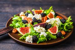 Salad with figs, feta cheese and blackberries in a wooden plate on dark background