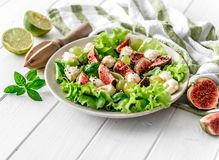 Salad with figs, mozzarella and grapes on a white wooden background. Stock Image