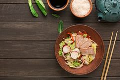 Salad with fish, onion, pepper and radish on wooden background. Asian restaurant healthy food. Salad with fish, onion, pepper and radish on wooden background Royalty Free Stock Photography