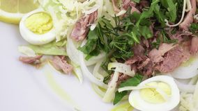 Salad with fish and quail eggs. Rotating salad with cheese, quail eggs, cucumber, parsley, lying on lettuce leaves stock footage