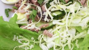 Salad with fish and quail eggs. Rotating salad with cheese, quail eggs, cucumber, parsley, lying on lettuce leaves stock video footage
