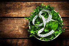 Salad with fitness  measuring tape over wooden background.  Die Stock Photos