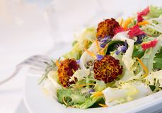 Salad of flowers. Isolated on a dinner table stock photography