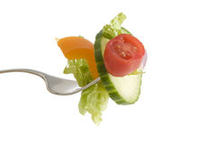 Salad on a Fork. A fork full of salad including cucumber, tomatoe, pepper and lettuce, isolated on a white background Stock Photography