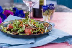 Salad of fresh arugula and pink grapefruit. Bright flowers. A glass of wine and a bottle. Romantic dinner royalty free stock photos