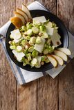 Salad of fresh Brussels sprouts, hazelnuts, cheese, raisins and. Pears closeup on a plate. Vertical top view from above Stock Photography