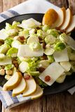 Salad of fresh Brussels sprouts, hazelnuts, cheese, raisins and. Pears closeup on a plate. vertical Stock Photo