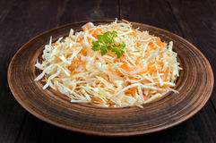 Salad of fresh cabbage and carrots in a clay bowl on dark wooden background Royalty Free Stock Images