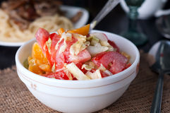 Salad with fresh cabbage. Tomato, cucumber and herbs on the plate on a table Stock Image