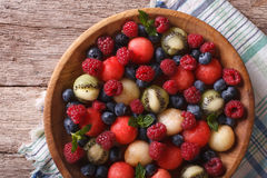 Salad of fresh fruits and berries closeup. horizontal top view. Salad of blueberries, raspberries, melon and watermelon in a wooden bowl closeup. horizontal view Stock Photos