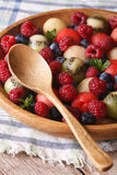 Salad of fresh fruits and berries in a wooden bowl closeup. vert. Fruit salad of blueberries, watermelon, raspberry, melon and kiwi in wooden bowl closeup Royalty Free Stock Photos