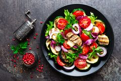 Salad with fresh and grilled vegetables and mushrooms. Vegetable salad with grilled champignons. Vegetable salad on plate. Healthy vegetarian food stock photography