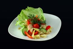 Salad with fresh lettuce leaves. Tomato, pepper on a black background Stock Photography