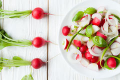 Salad of fresh radishes and radish with leaves on the table. Closeup Stock Photo