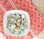 Salad of fresh radishes, spinach and pomegranate. With sour cream on rustic cloth with a red pattern. top view Stock Image