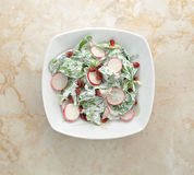 Salad of fresh radishes, spinach and pomegranate. With sour cream. top view Royalty Free Stock Photo