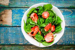 Salad with fresh spinach and strawberries with balsamic sauce and sesame Royalty Free Stock Photos