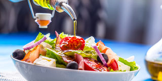 Salad. Fresh Summer Lettuce Salad.Healthy Mediterranean Salad Olives Tomatoes Parmesan Cheese And Prosciutto. Pouring Olive Oil Stock Photo