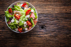 Salad. Fresh summer lettuce salad. Healthy mediterranean salad olives tomatoes parmesan cheese and prosciutto royalty free stock photos